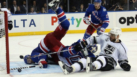 Rangers defenseman Dan Girardi falls on his face to poke the puck away from Marian Gaborik of the Los Angeles Kings, right, after colliding with goalie Henrik Lundqvist on Monday night.