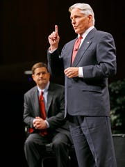 Democrat Fred DuVal makes a point during the debate Tuesday night, as Republican Doug Ducey looks on. DuVal stressed that funding and improving the state's education system is key to improving its economy.