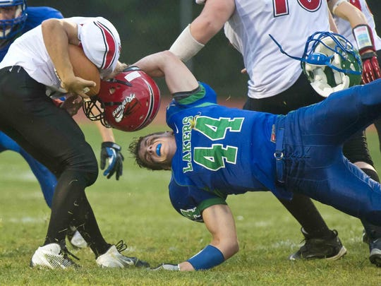 Colchester's Grant Cummings (right) loses his helmet as he tries to tackle Champlain Valley Union's Andrew Bortnick in a 2013 high school football game.