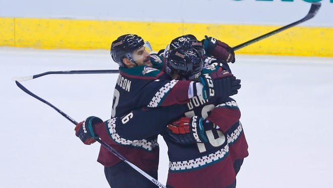 The Coyotes' Brad Richardson (left) grabs Max Domi (front) and Oliver Ekman-Larsson after a goal from Ekman-Larsson in overtime at Gila River Arena on Nov. 27, 2015, in Glendale.