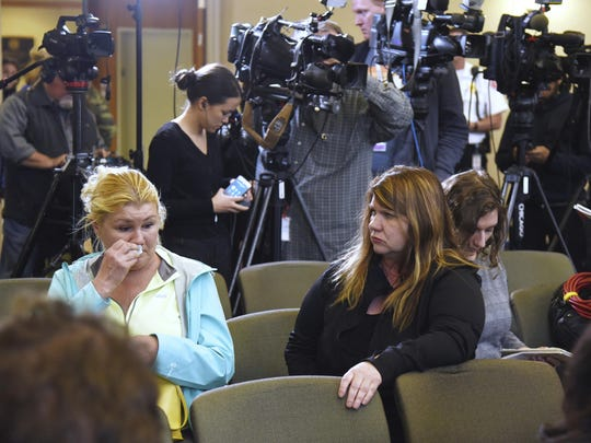 "Long time Crystal Lake resident Danielle Hein, left, wipes away tears after sitting in a press conference at the Crystal Lake village hall where officials announced charges against the parents of Andrew ""AJ"" Freund for his death, Wednesday, April 24, 2019."