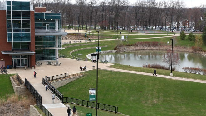 Students walk past the Student Center on the Eastern Michigan University campus in Ypsilanti on Thursday April 16, 2015.