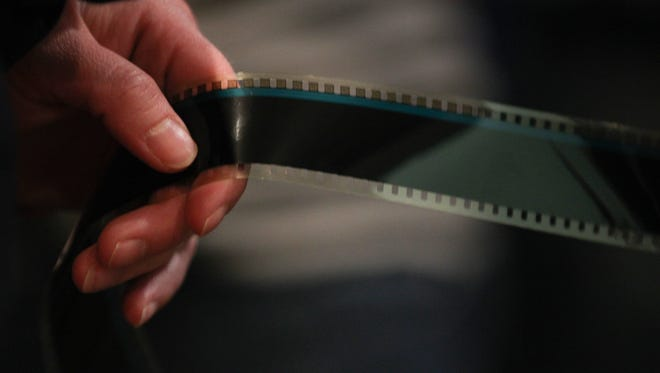 A strip of film is used for a ribbon cutting ceremony at FilmScene on Tuesday, Feb. 2, 2016.