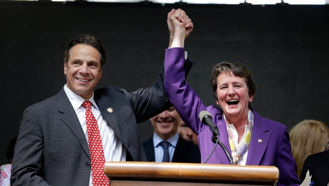 New York Gov. Andrew Cuomo, left, and International President of the Service Employees International Union Mary Kay Henry gesture during a rally after the New York Wage Board endorsed a proposal to set a $15 minimum wage for workers at fast-food restaurants with 30 or more locations, Wednesday, July 22, 2015 in New York.