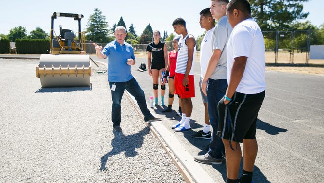 New Mckay High School Principal Rob Schoepper, left, talks to students about construction on the school's new turf field on Tuesday, Aug. 1, 2017. Schoepper is started his first year at McKay, after formerly working as the principal at Claggett Creek Middle School.