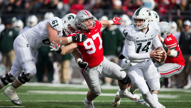 Ohio State's Nick Bosa is blocked by Michigan State's Cole Chewins as quarterback Brian Lewerke looks for an open receiver in the first half Saturday at Ohio Stadium.