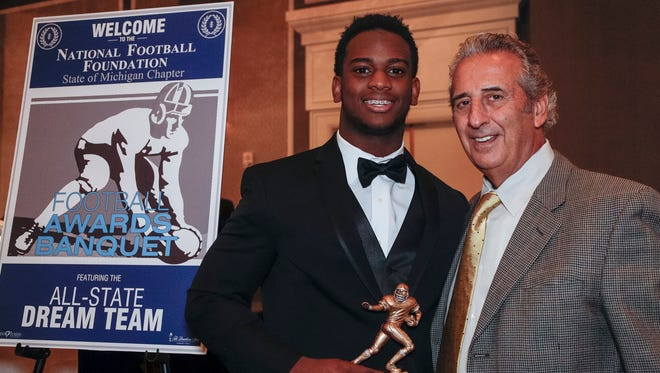 Detroit Free Press 2017 All-State Dream Team member Marcel Lewis of Clinton Township Chippewa Valley poses for a photo with N.F.F. State of Michigan Chapter president Tony Versaci during the National Football Foundation State of Michigan Chapter awards banquet at the Dearborn Inn in Dearborn on Dec. 10, 2017.