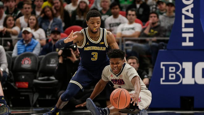 Detroit Mercy guard Jermaine Jackson Jr. tries to protect the ball as he falls in front of Michigan guard Zavier Simpson in the second half of the Hitachi College Basketball Showcase at Little Caesars Arena in Detroit, Saturday, Dec. 16, 2017.