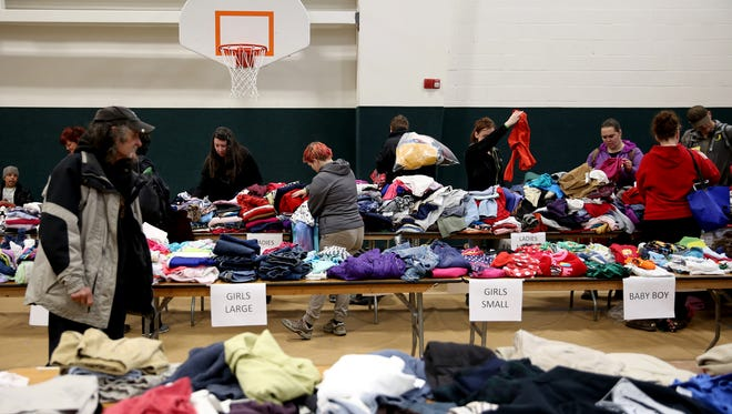 People look through tables of clothing available to take during the 10th annual Marion County Community Homeless Connect at Salem First Baptist Church on Tuesday, March 27, 2018. The event featured 55 different service providers to give underserved people access to medical care, bike repair, pet grooming, clothing, sleeping bags, haircuts and more.