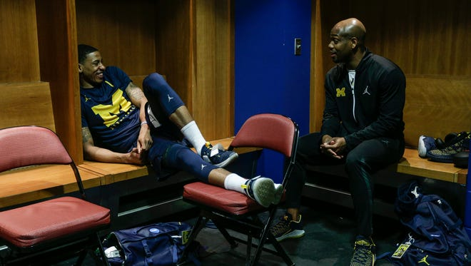 Michigan guard Charles Matthews, left, talks to assistant coach DeAndre Haynes in locker room at INTRUST Bank Arena in Wichita, Kan., on Friday, March 16, 2018.