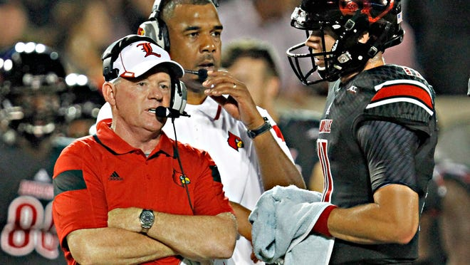 Louisville head coach Bobby Petrino, left, talks with quarterback Will Gardner, right, during a timeout in an NCAA college football game against Miami in Louisville, Ky., Monday, Sept. 1, 2014. At center is offensive coordinator Garrick McGee.