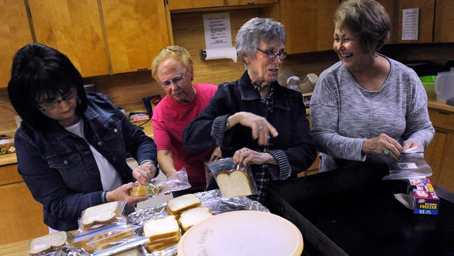 Teresa Lampman (left), Christa Coulter, Gayle Stroud, and Gail Neeley talk and laugh as they wrap-up extra sandwiches Wednesday Feb. 8, 2017. On the second Wednesday of each month, De Leon's First United Methodist Church holds a no-cost Shared Table dinner for members of the community.