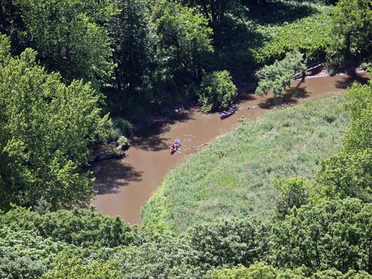 Canoers paddle down the Kickapoo River past Wildcat