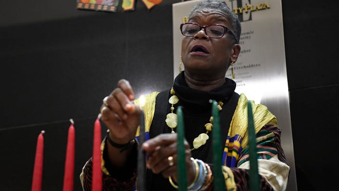 Barbara Taylor-Rosser lighting the candles of the kinara and going over the symbols and seven principles of Kwanzaa during a ceremony at One Bergen County Plaza in Hackensack on Tuesday.