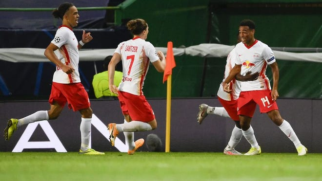 Leipzig's Tyler Adams, right, celebrates with teammates after scoring his team's second goal during the Champions League quarterfinal match between RB Leipzig and Atletico Madrid at the Jose Alvalade stadium in Lisbon, Portugal, Thursday, Aug. 13, 2020.
