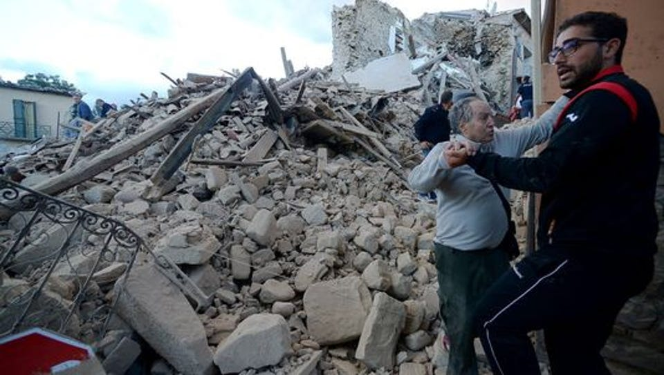 Residents stand among damaged buildings Wednesday after
