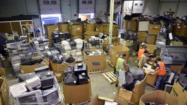 Workers sort electronic equipment at Good Point Recycling in Middlebury.