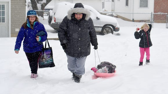 Jadyn Bussard, 11, walks beside Lee Tripp, who pulls a sled filled with various items, as Abigail Tripp, 8, fixes her hair as snow falls in Staunton.