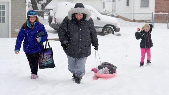 Jadyn Bussard, 11, walks beside Lee Tripp, who pulls
