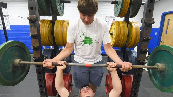 A senior, Gabe Glover of Fort Defiance High School spots for and assists Alex Niculescu, a sophomore with Down syndrome, who is bench pressing weights during gym class at the school on Wednesday, May 17, 2017. Glover assists Niculescu each school day during the sophomore's gym class.