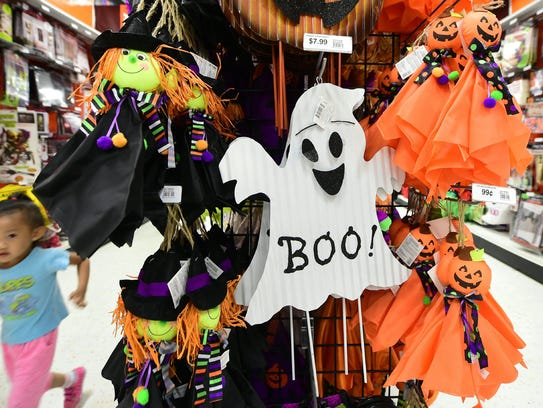 a child runs to keep up with her mom past items displayed - Halloween Stores In Toms River Nj
