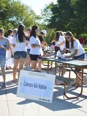 Volunteers put together literacy kits during Saturday's Day of Action in Washington Park in Two Rivers.