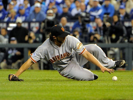 Oct 21, 2014; Kansas City, MO, USA; San Francisco Giants starting pitcher Madison Bumgarner slides to field a ball hit by Kansas City Royals first baseman Eric Hosmer (not pictured) in the 6th inning during game one of the 2014 World Series at Kauffman Stadium. Mandatory Credit: John Rieger-USA TODAY Sports