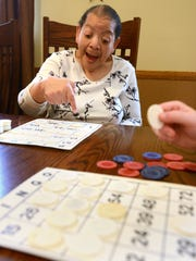Irene Collins points to a number on her bingo board at the Carr Center while playing the game with other members of the center's adult day care program.