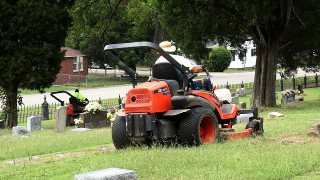 Fort Smith Parks and Recreation maintenance workers mow between headstones in Oak Cemetery, 1401 S. Greenwood Ave., in September 2020. A  nonprofit organization called Fort Smith Cemeteries Inc. was recently founded to help the city maintain this and several other cemeteries in the city. Oak Cemetery is on the National Register of Historic Places and is one of the oldest burial sites in Arkansas. The oldest monument there is dated 1842. [JAMIE MITCHELL/TIMES RECORD}