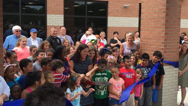 Hobgood Elementary School Principal Tammy Garrett cuts the ceremonial ribbon in front of the new wing at Hobgood Elementary School on Saturday afternoon.