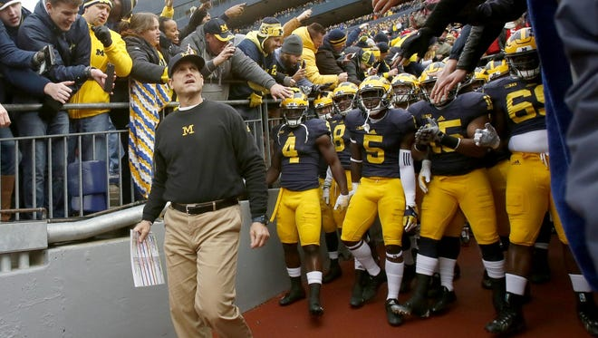 Michigan coach Jim Harbaugh leads his players out of the tunnel before their game against Ohio State on Nov. 28. A victory Friday would give U-M a 10-win season.