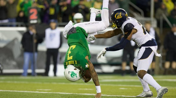 Nov 7, 2015; Eugene, OR, USA; Oregon Ducks quarterback Vernon Adams Jr. (3) leaps over California Golden Bears safety Stefan McClure (21) to score a touchdown in the second quarter at Autzen Stadium. Mandatory Credit: Scott Olmos-USA TODAY Sports