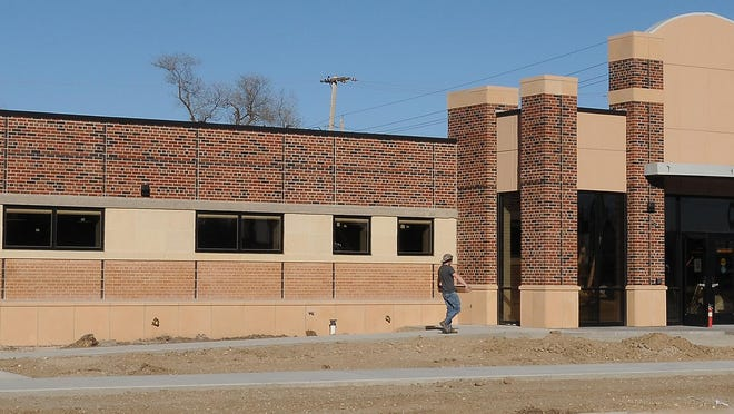 Construction workers move material into the new Nursing Education Center at Kansas Wesleyan University, located in a former medical office building at 135 E. Claflin. The $5.5 million building is scheduled to be finished by the end of this year.