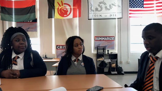 """Jaquinsia Armstrong 17, and Tieranee Carr, 18, listen to . Wazairean Harris, 17, talk about where he believes Memphis rapper Yo Gotti falls short in being a role model. """"Sure, he advocates against teen violence, and he's given us jobs, but then he raps about how you never had to punch a clock because you were cooking [cocaine] in a kitchen,"""" he said,"""