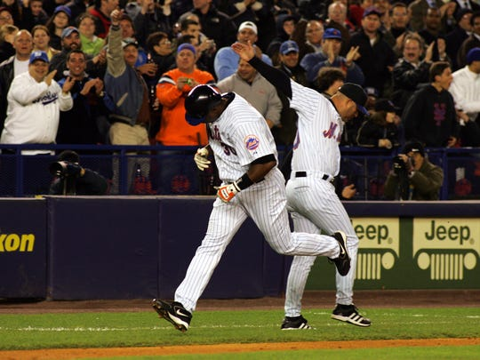 Mets player Cliff Floyd high-fives third base coach Manny Acta after 2-run HR against the Braves in April 2005.