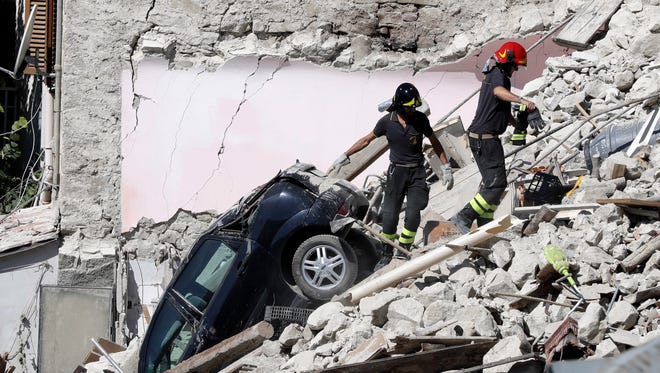 Rescuers make their way through destroyed houses following Wednesday's earthquake in Pescara Del Tronto, Italy, Thursday, Aug. 25, 2016. Rescue crews raced against time Thursday looking for survivors from the earthquake that leveled three towns in central Italy, but the death toll rose to 247 and Italy once again anguished over trying to secure its medieval communities built on seismic lands.  (AP Photo/Gregorio Borgia) ORG XMIT: GB112