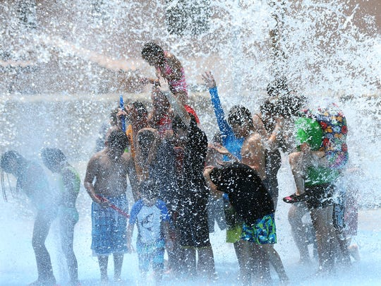 Children wait to get dowsed by a large bucket of water that tips over when full at the Marty Robbins Spray Park at 11600 Vista Del Sol Drive as the temperature reached the triple-digit mark Tuesday in East El Paso. The spray park is among eight operated by the city of El Paso.
