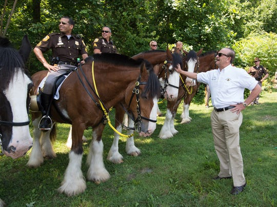 New Castle County Executive Thomas P. Gordon talks with a member of the New Castle County Police Department's Mounted Patrol Unit at the New Castle Ice Cream Festival earlier this year.