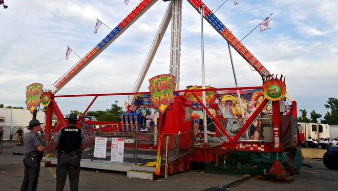 Authorities stand near the Fire Ball amusement ride after the ride malfunctioned injuring several at the Ohio State Fair, Wednesday, July 26, 2017, in Columbus, Ohio. Some of the victims were thrown from the ride when it malfunctioned Wednesday night, said Columbus Battalion Chief Steve Martin.