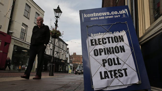 A man walks past a board advertising a local news website with coverage regarding the Nov. 20 special election, in Rochester, England, on Nov. 19, 2014.
