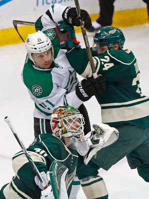 Wild goalie Devan Dubnyk pays no attention as Wild's Matt Dumba, right, keeps Dallas Stars' Antoine Roussel of France at bay during the first period of Game 4 on Wednesday.