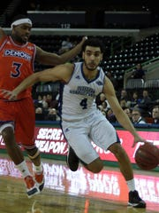 The Islanders' Ehab Amin (4) drives past Northwestern State's Devonte Hall for two of his 28 points in A&M-Corpus Christi's 99-82 win over the Demons Saturday night.