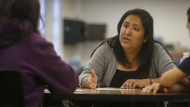 Isabel Conn speaks with a woman who needed immigration-related guidance for her family during a program on Tuesday, April 11, 2017, at North High School in Des Moines.