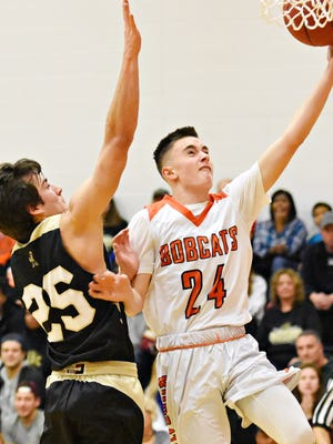 Northeastern's Andrew Brodbeck, left, takes the ball to the net while Delone Catholic's Evan Brady defends during Bobcat Tip-Off Classic basketball action at Northeastern High School in Manchester Township, Friday, Dec. 8, 2017. Northeastern would win the game 80-40. Brodbeck scored five points off the bench, one of several bench players for the Bobcats to score in the game, showcasing the team's depth. Dawn J. Sagert photo