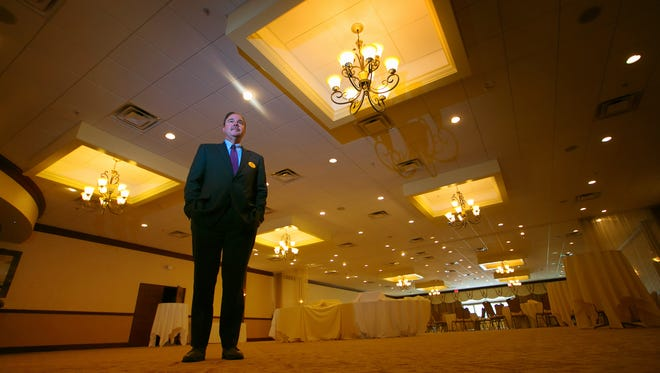 Paul Rada, general manager at Clarion Hotel-The Belle in Minquadale, stands under the electric lights of the Golden Bell Ballroom. Rada says the utility bill increase would mean an additional $6,000 a month bill for the hotel.