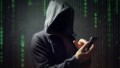 Computer hacker with mobile phone smartphone stealing