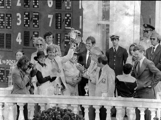 Mickey Taylor held up the winning trophy yesterday after Gov. Julian Carroll, clapping, presented it to Seattle Slew's owners. Seattle Slew was ridden by ridden by Jean Cruguet on May 7, 1977.