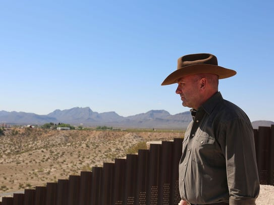 Higgins peers over the border near El Paso, Texas.