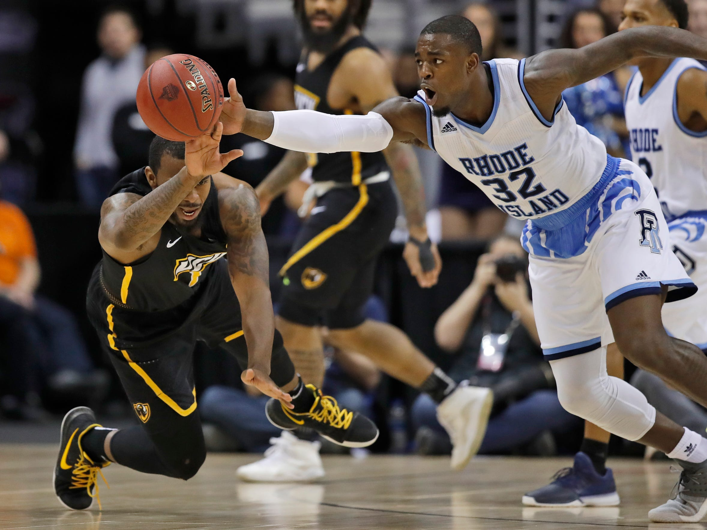Rhode Island guard Jarvis Garrett, left, loses the ball after he was fouled by Rhode Island guard Jared Terrell, right, during the first half of an NCAA college basketball quarterfinal game in the Atlantic 10 Conference tournament, Friday, March 9, 2018.
