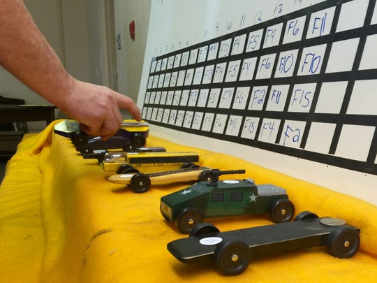 Officials organize the cars used in the derby.